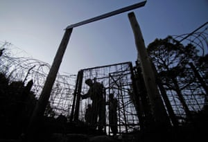 Indian army soldiers patrol near the border fencing at the Line of Control that divides Kashmir between India and Pakistan.
