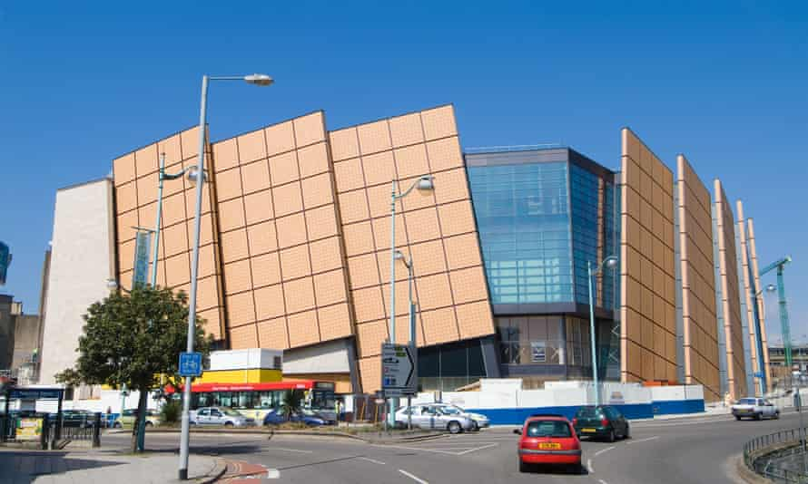 View from across the street of Drake Circus, a striking modern building with large brown facade panels arranged at an angle to the vertical around a glass entrance