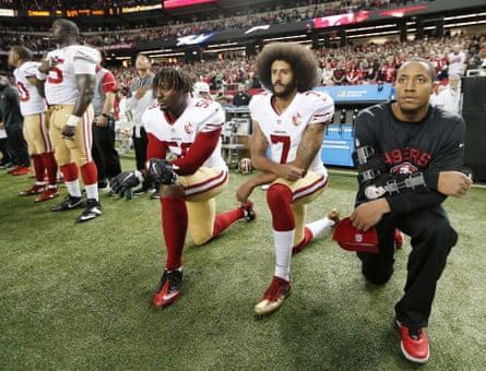 Colin Kaepernick (7) and outside linebacker Eli Harold (58) kneel