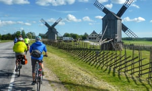A group of cyclists pass working windmills on tranquil Saaremaa island, Estonia.