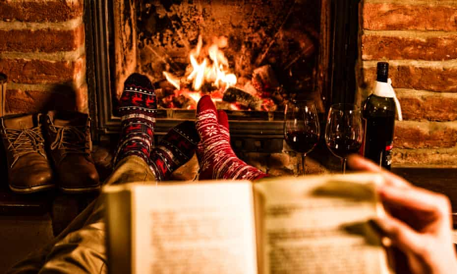 Couple reading a book with their feet up in front of fire