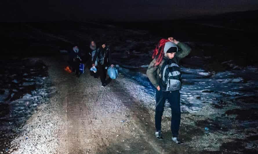 Migrants walk through the night in freezing temperatures after crossing the Macedonian border into Serbia.