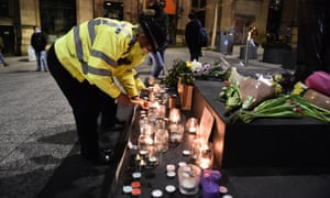 A female police officer lights a candle next to a makeshift memorial on Market Square in Nottingham.