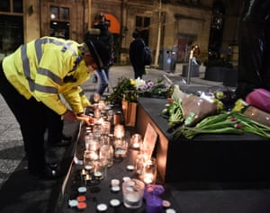 A female police officer lights a candle next to a makeshift memorial during a vigil for Sarah Everard on Market Square.