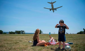 Children in a field with a passenger jet flying over them