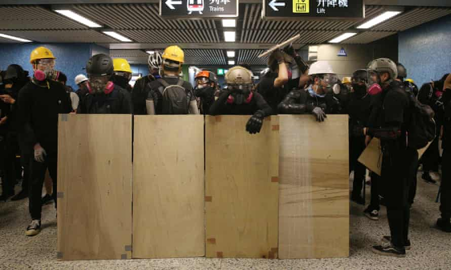 Anti-extradition bill protesters stand behind makeshift shields in Lam Tin station