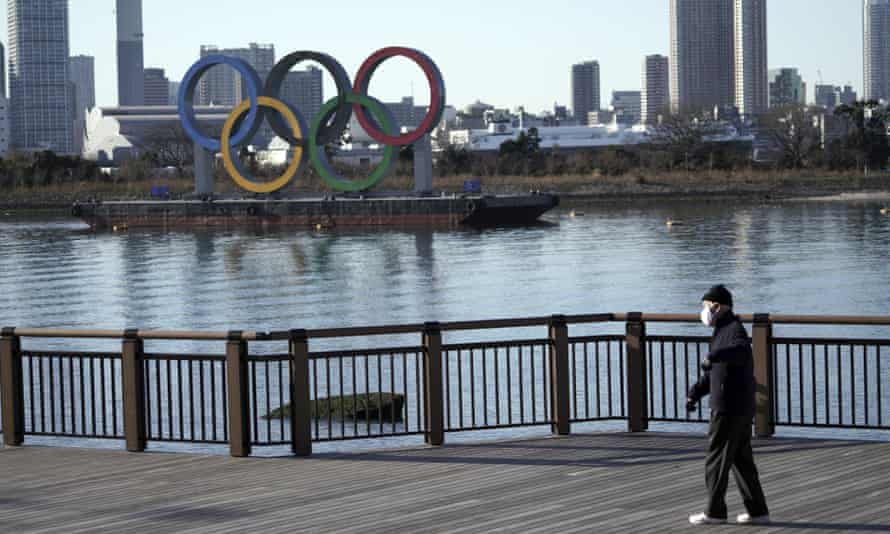 A man walks past the Tokyo 2020 Olympic rings wearing a mask