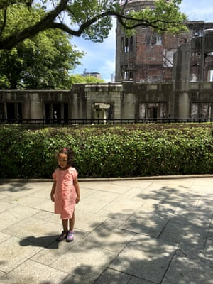 My daughter posing in front of the skeletal remains of the Atomic Bomb Dome during our 2017 trip.