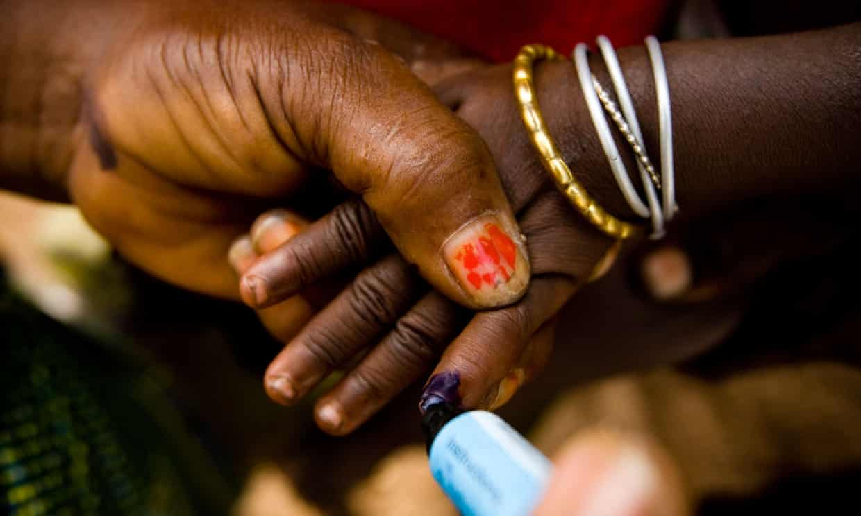A community volunteer marks the finger of a child with ink during a polio immunisation exercise. Photograph: Olivier Asselin/Alamy