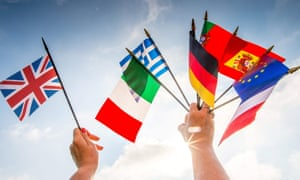 A person holds European country flags in an hand and a United Kingdom flag in another