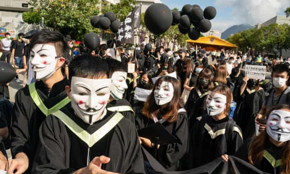 Hong Kong students wearing Guy Fawkes masks march at the Chinese University of Hong Kong campus as they chant anti-government protest slogans