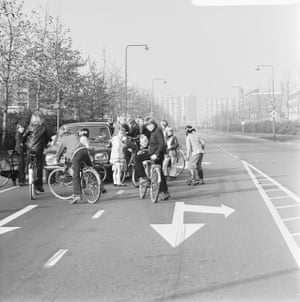 Group of cyclists around a parked car on a deserted road