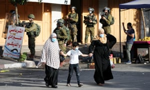 Palestinians and Israeli soldiers during protests against an agreement between Israel and the UAE in the West Bank city of Hebron, September 2020