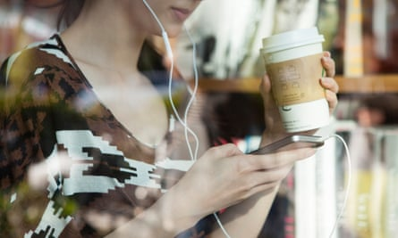 woman listening to smartphone in coffee shop