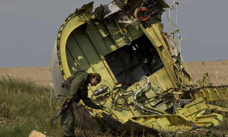 A pro-Russian rebel with wreckage at the crash site near the village of Hrabove, eastern Ukraine, in July 2014.