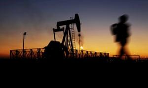 A boy walks by an oil pump at sunset in the desert oil fields of Sakhir, Bahrain