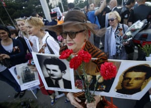 A woman carries pictures of her relatives killed in the war, during the Victory Day parade at the memorial cemetery in Belgrade, Serbia