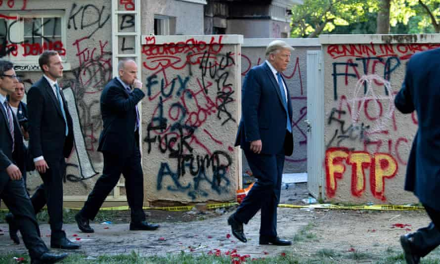 Donald Trump walks back to the White House escorted by the Secret Service after appearing outside of St John's Episcopal church across Lafayette Park on Monday.