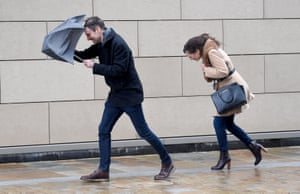 People struggle with wet and windy weather in Manchester