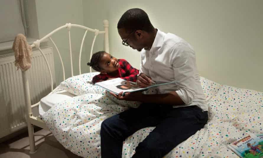 Robert reads a bedtime story with his daughter, Forefoluwa, 3, in their home in London