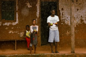 A man and boy wash mangoes in the rain in Pelundo.