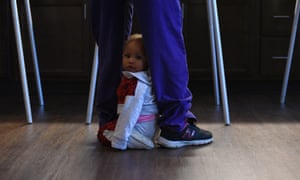 Raleigh, North Carolina Mela, 11 months, sits in-between grandmother Helen McCullers, legs, as McCullers votes for the 2016 US presidential election at the Walnut Terrace office