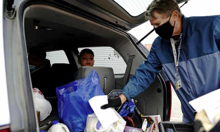 Victor Alvarado Garcia, nine, watches a volunteer put food inside his family's car outside the Walworth County Food Pantry in Elkhorn, Wisconsin, in October.