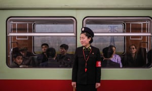 A guard waits for passengers to board a train on the metro, in Pyongyang, North Korea.