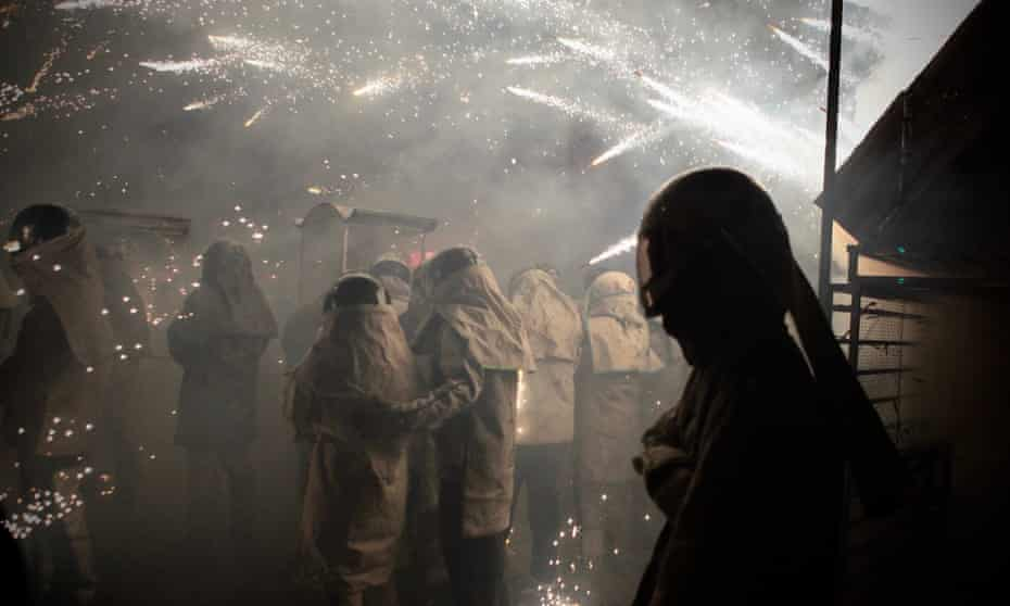 People wear protective clothing as they stand among the flaming projectiles