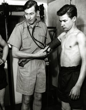 10th February 1957. Dr. Bannister checking on a British army volunteer, one of a group that had agreed to take part in an experiment to study the body's reaction to high temperatures.