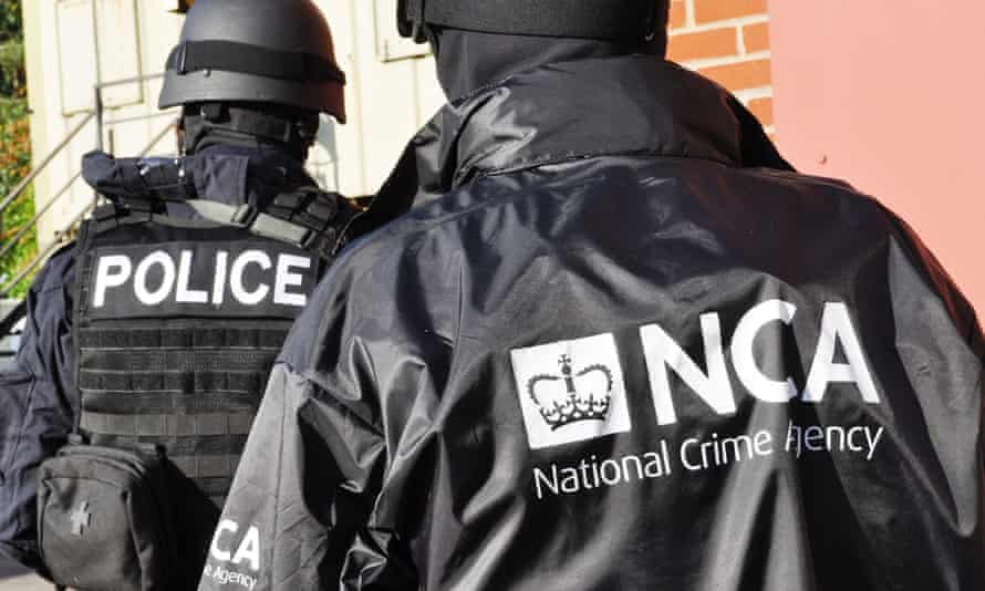 Police and NCA officers approach a property