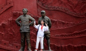 A girl takes a selfie with statues depicting late Chinese chairman Mao Zedong (L) and former general Zhu De.