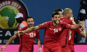 Mohamed Ben Amor, no 14, leads the celebrations amongst the Tunisian players after Algeria's Mandi scored an own goal.