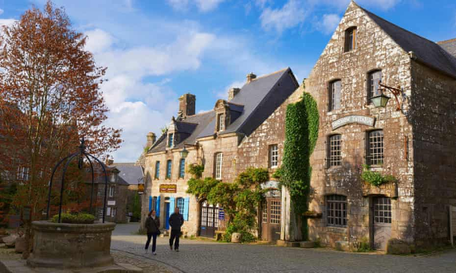 Two people walking through Locronan village in Brittany, past old stone buildings.