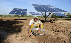 Woman in field with solar panels.