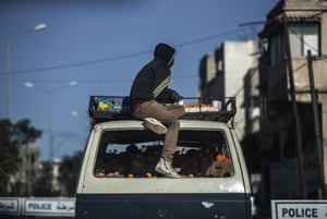 A Palestinian man sits on top of a vehicle loaded with boxes of oranges while passing a police checkpoint in the southern Gaza Strip.