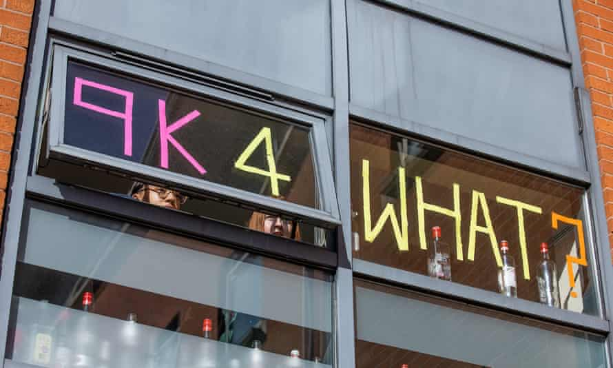 Students at Manchester Metropolitan University look out of their window, which they have marked with '9K 4 WHAT?', 27 September 2020.