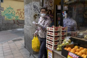 A woman leaves a fruit store in Madrid wearing a protective mask and gloves