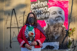 A woman holds a rose in front of banner on graffitied wall.