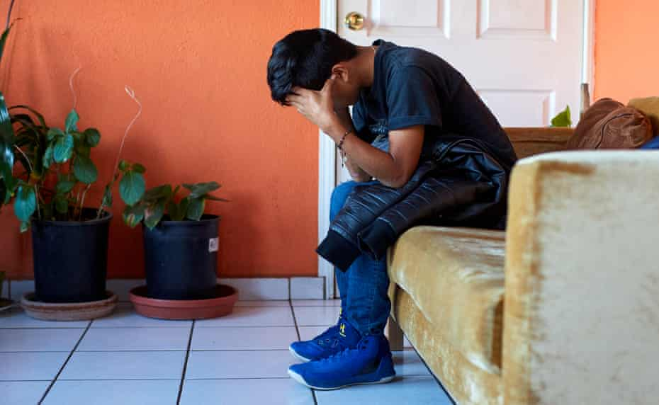 A deported minor calls his family after being picked from the Desarrollo Integral de la Familia offices to the YMCA shelter.