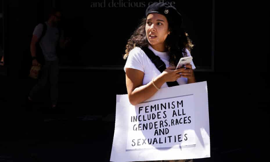 young women in black beret with a sign that says feminism includes all genders races and sexualities