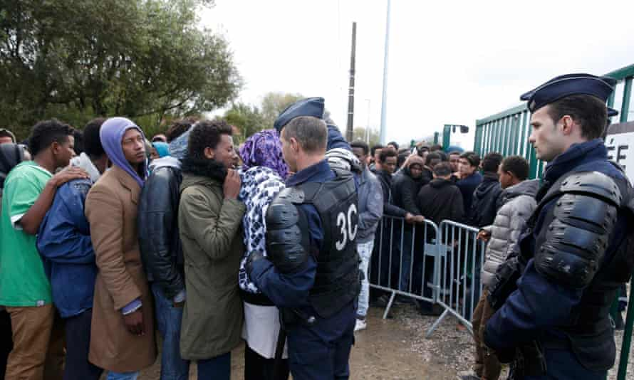 French riot police alongside a queue of younger migrants in the Calais camp, preparing for the facility to be shut down and cleared over the first few days of this week.