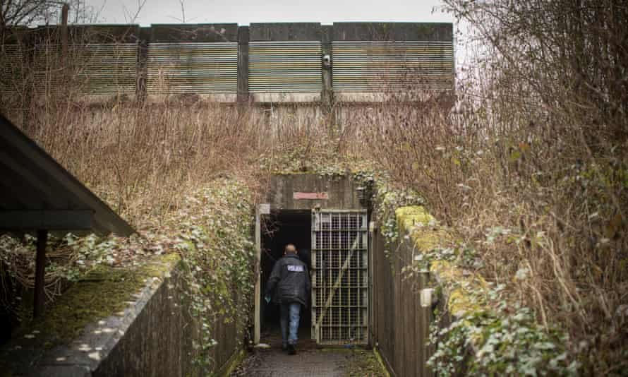 A police officer enters the bunker.