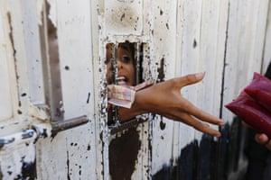 Children buy ice-cream through a gap in their school gate in Sana'a, Yemen
