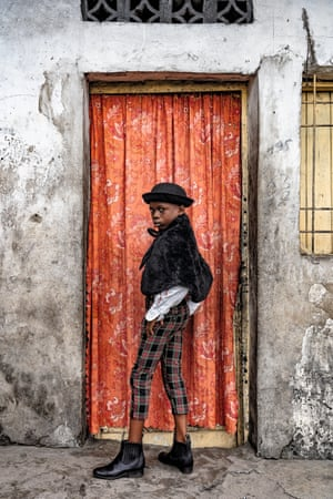 Natan Mahata, eight-year-old school student and sapeur for three years, in Kinshasa. La Sape is a constantly evolving movement, as disenfranchised youths use fashion as a way of navigating their nations' journeys from developing countries into more cosmopolitan futures. Natan Mahata wears jacket and hat by Zara, trousers by Place, shirt by Pierre Cardin, braces by Boris and shoes by JM Weston