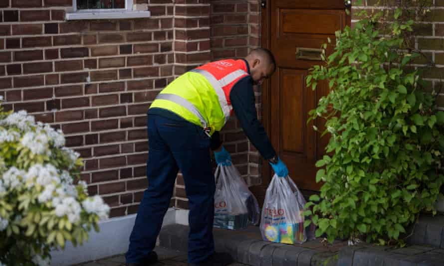 A Tesco worker delivers supplies to a vulnerable householder.