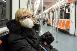 A woman wearing a protective face mask sits in an empty metro carriage in Rome