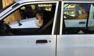Drivers wearing face masks in Tehran on Sunday.