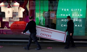 A worker attaches a poster notifying customers about tier 4 coronavirus restriction in central London.