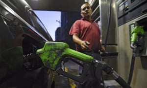 A worker puts gas to a vehicle in Caracas